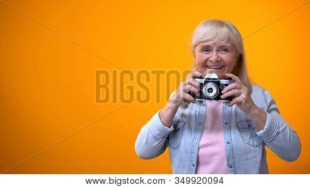 Smiling Retiree Woman Taking Photo With Vintage Camera, Hobby And Relaxation
