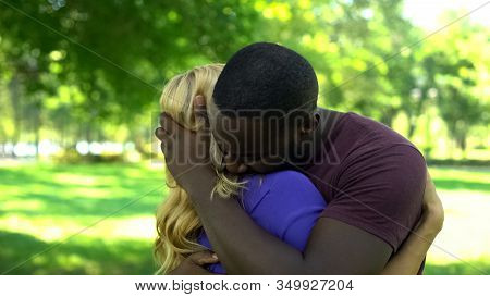 Upset Multiracial Couple Embracing, Together Despite Society Stereotypes, Crisis