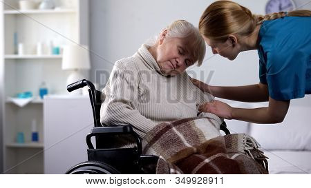 Young Volunteer Waking Up Old Woman Sleeping In Wheelchair, Hospital Care