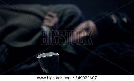 Paper Cup On Floor, Miserable Beggar Lying On Background, Asking For Money
