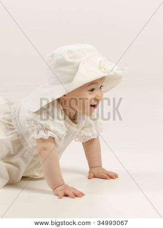 little child baby girl sitting on the floor indoors in baby room smiling  hat dress fashion