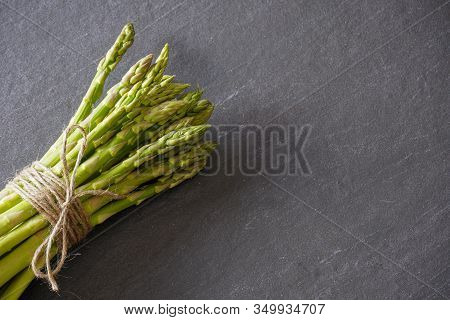 View From Above Of A Bundle Of Green Asparagus From Above Tied With Twine On A Gray Slate Counter Wi