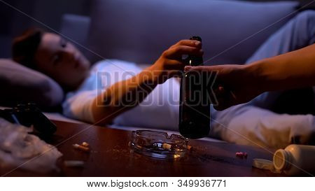 Hand Offering Addicted Young Male Bottle Of Beer, Detrimental Alcohol Abuse