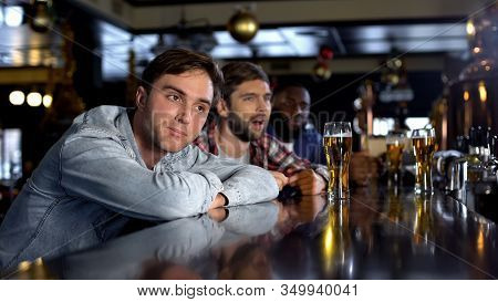 Disappointed Male Friends Watching Game In Pub, Disappointed With Losing Match