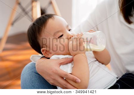 Close-up Of Asian Mother Babysitting And Feeding Her Own Son With Milk Bottle In Living Room At Home
