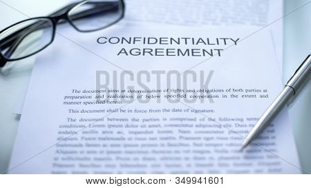 Confidentiality Agreement, Lying On Table, Pen And Eyeglasses On Document