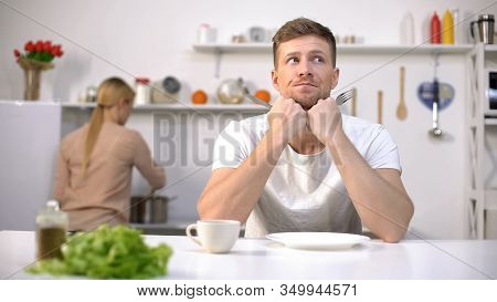 Anxious Husband Waiting For Lunch, Wife Cooking On Background, Lack Of Time