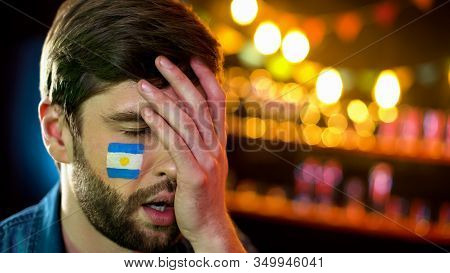 Argentinian Football Fan With Flag On Cheek Making Facepalm, Unhappy With Loss