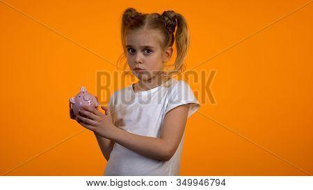 Upset Little Girl Holding Empty Piggybank, Having No Money, Insufficient Savings
