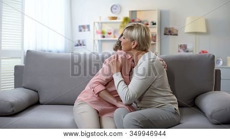 Unhappy Mature Female And Daughter Hugging On Sofa, Loss Breakup And Support