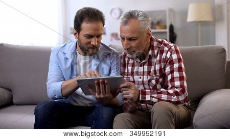 Retiree Father And Middle Aged Son Scrolling Tab, Watching Photos From Vacation