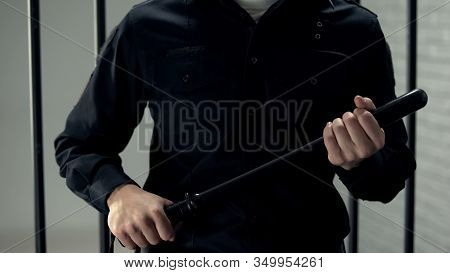 Prison Security Guard Standing Near Cell With Truncheon, Strict Regime, Violence