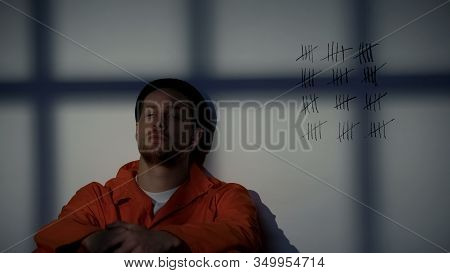 Prisoner Sitting In Jail With Crossed Lines On Wall, Serving Long Imprisonment