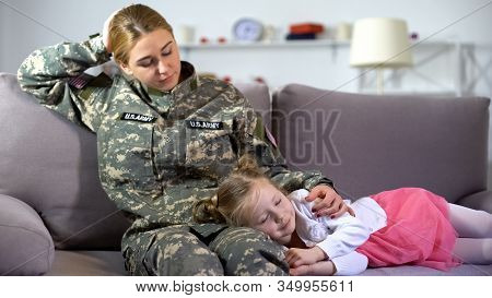 Caring American Military Mother Stroking Little Kid Sleeping On Sofa, Homecoming