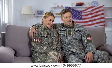 Cheerful Couple Of Soldiers Sitting On Sofa Against Us Flag, Happy Homecoming