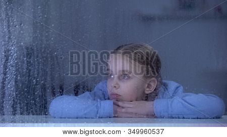 Girl Lying Window Sill On Rainy Day, Orphan Kid Dreaming About Home, Loneliness
