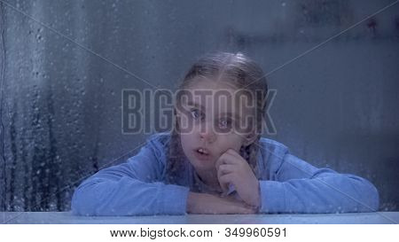 Sad Little Girl Looking At Camera Through Rainy Window, Forgotten By Parents