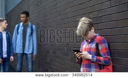 Junior Student Using Cell Phone Standing Lonely In Backyard, Outcast In School