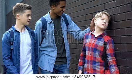 Cruel Students Bullying Boy In Backyard, Punching Head, Physical Intimidation