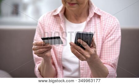 Senior Female Entering Credit Card Number On Smartphone, Paying Bills Online