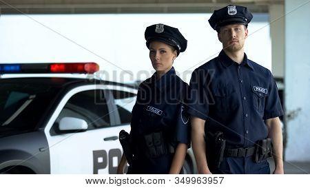 Two Serious Policemen In Uniform And Service Cap Posing Near Patrol Car, Order
