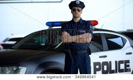 Brave Police Officer In Service Cap And Sunglasses Posing Into Camera Near Car