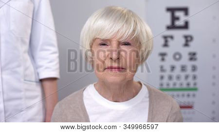 Elderly Lady Visiting Friendly Optometrist, Checking Vision, Risk Of Cataract