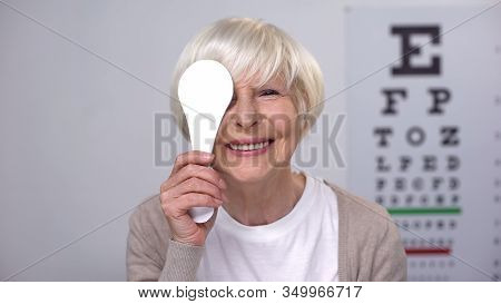 Retired Female Closing Eye And Smiling To Camera, Successful Cataract Surgery
