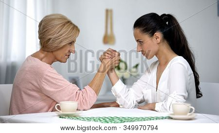 Mother And Daughter-in-law Looking On Each Other During Arm Wrestling Battle