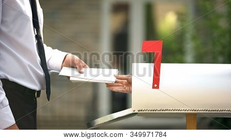 Man Receiving Letters And Bills In Mailbox In Front Of House, Mail Delivery