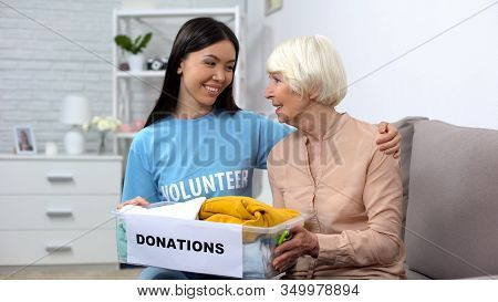 Happy Female Volunteer And Aged Woman Holding Donation Box, Humanitarian Aid