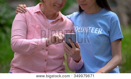 Mature Woman And Young Volunteer Looking Smartphone Photos Together, Assistance