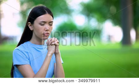 Asian Female Praying Outdoors Joining Hands, Religious Belief, Asking For Help