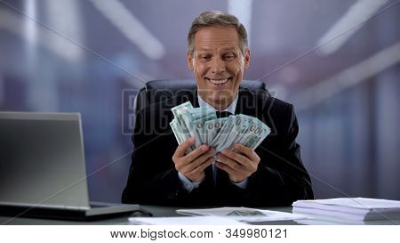 Greedy Businessman Holding Bunch Of Dollars, Rejoicing Easy Income, High Salary