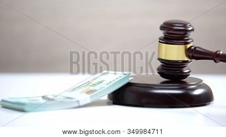 Bunch Of Dollars On Table, Gavel Standing On Sound Block, Damage Compensation