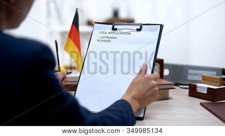 Immigration Inspector Denying Visa Application, German Flag On Table, Embassy