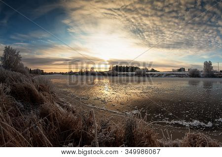 The Sun Rises Over The Rive On A Cold Morning At The Rural Finland. The River Water Is Slowly Freezi