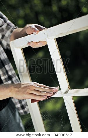 Man using a piece of abrasive sandpaper on an old window frame.