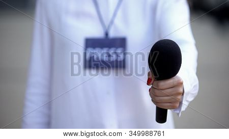 Journalist With Press Id Proposing Microphone For Interview, Television News
