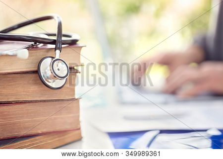 Doctor or student at medical college with stack of books and stethoscope
