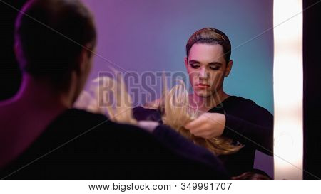Good-looking Travesty Diva Putting On Blond Wig, Preparing For Transgender Party