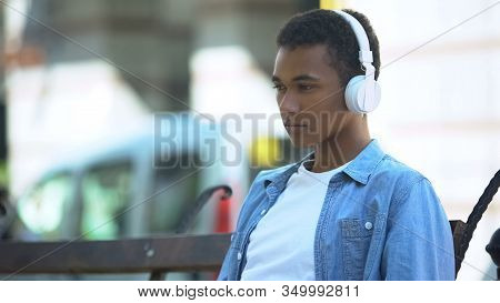 Sad Mixed-race Boy Listening To Favorite Romantic Song, Yearning On Bench