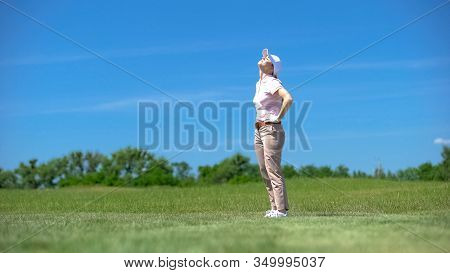 Inexperienced Woman Golfer Dissatisfied About Failed Shot, Looking Up, Loser
