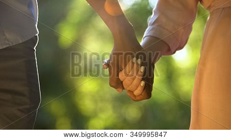 Multiracial Couple Holding Hands At Sunny Park, Romantic And Intimacy, Close-up