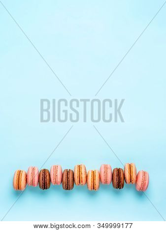 Macarons With Copy Space. Row Of Perfect French Macarons Or Macaroons On Blue Background. Top View O