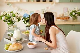 Mother's Day Greeting Card. Family Mother And Baby Daughter In Morning Have Breakfast In Kitchen. Sp