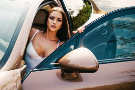 Young Brunette Lady In Glamorous Lingerie With Sexy Bust Sitting At Driver Position In Golden Expens