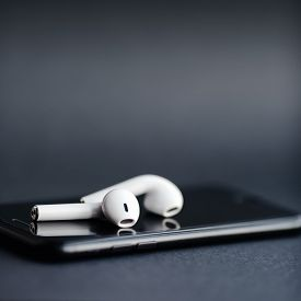 Smartphone and wireless earphones isolated on the grey background.