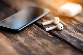 Smartphone And Earphones, Close Up Isolated On The Wooden Background.