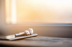 Smartphone and wireless earphones, close up isolated on the wooden background.
